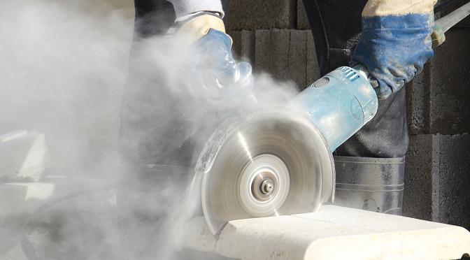 Worker grinding stone creating huge hazardous cloud of dust